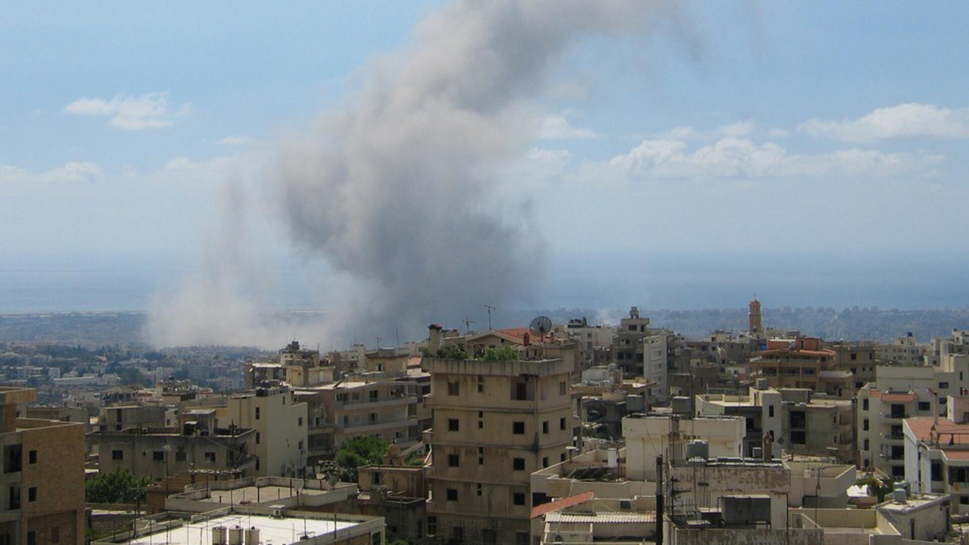 The skyline of Beirut with a huge plume of smoke in the background.