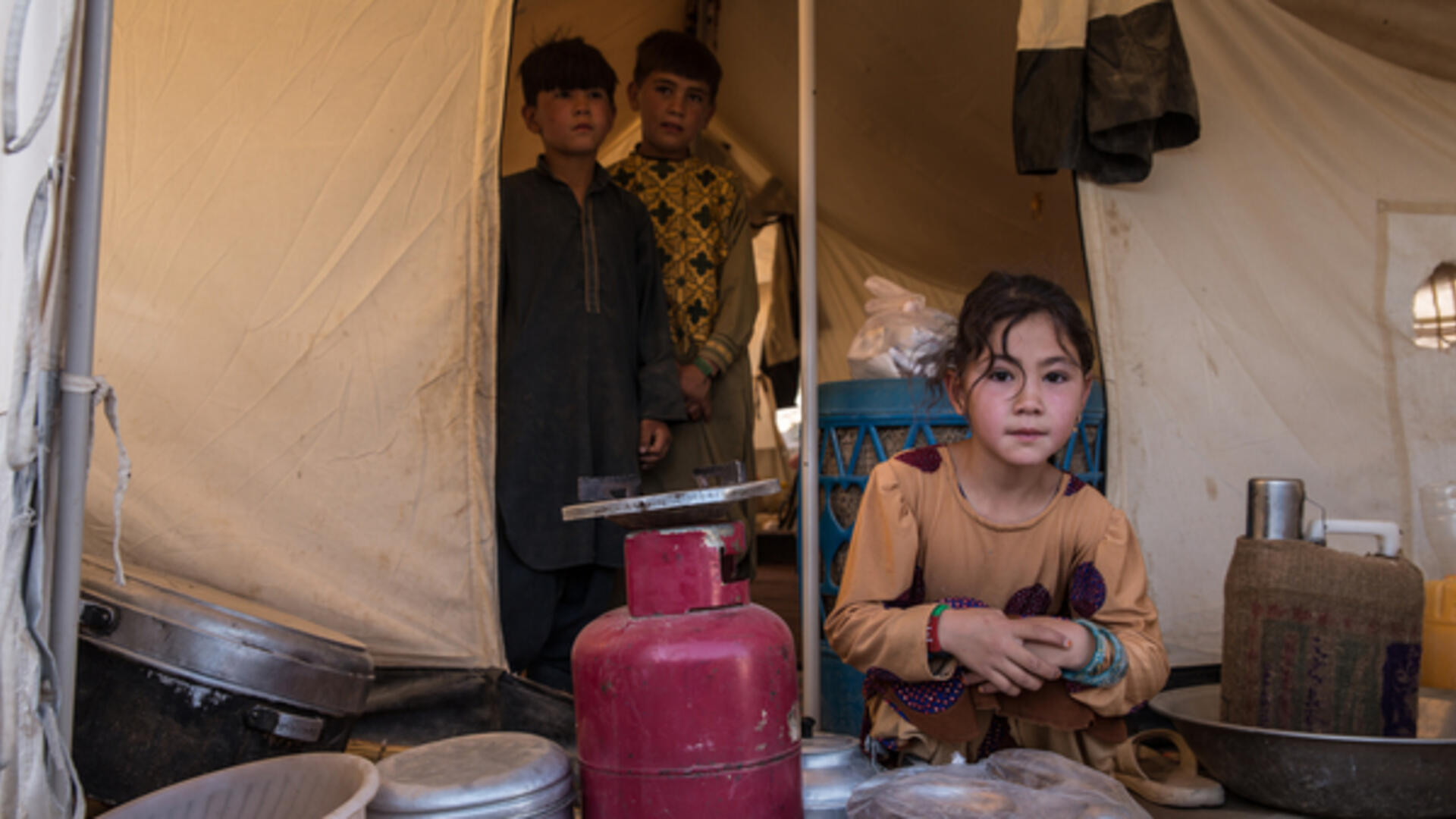 Three children at the entrance to a tent in Badghis, Afghanistan where their family is living after being displaced by drought.