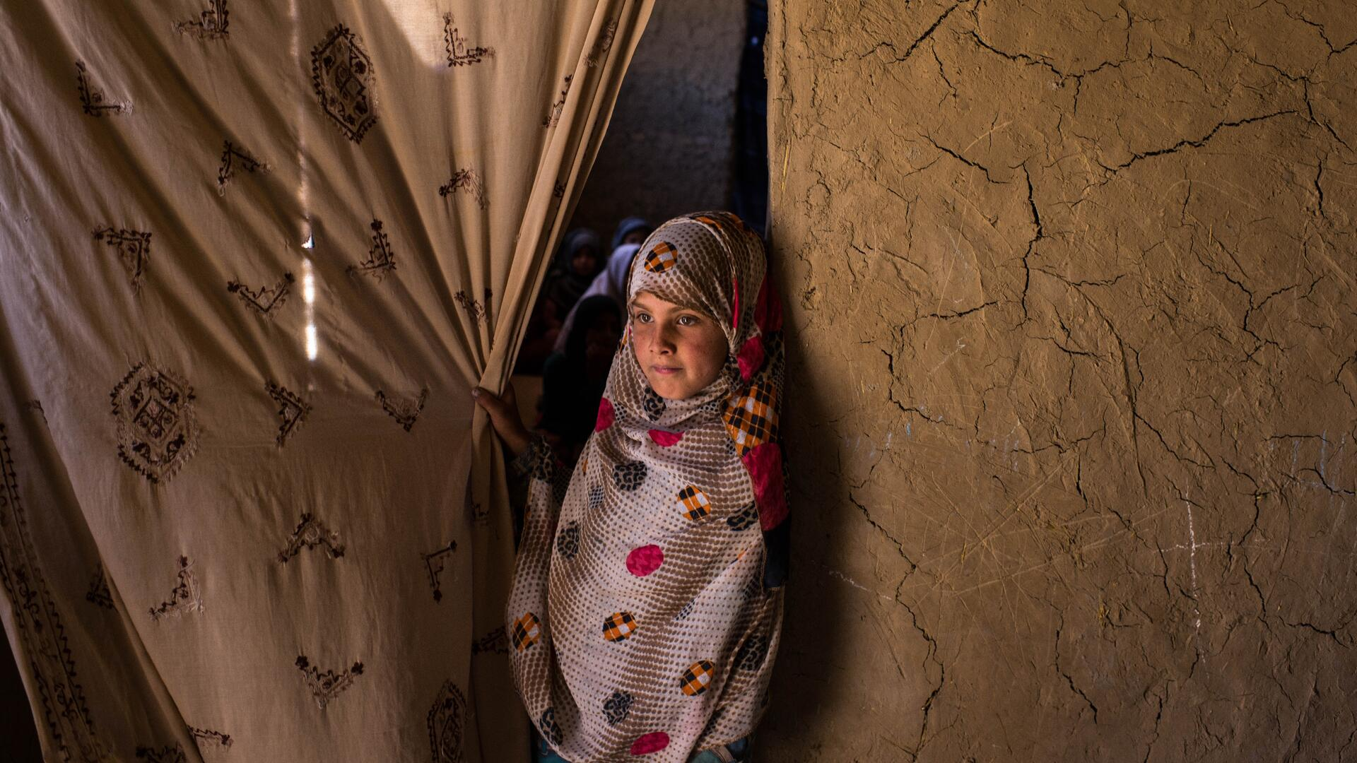 A young girl stands at the entrance to her classroom in Kabul, pulling back a curtain in the doorway and looking into the distance.
