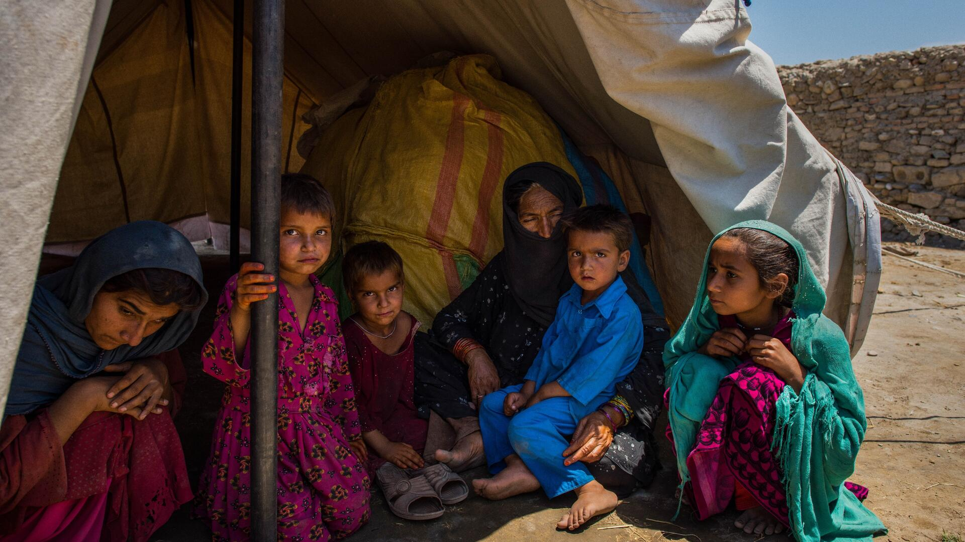 Women and children sit in the shade of one of their family's tents in a displacement camp in a desert landscape in Afghanistan..