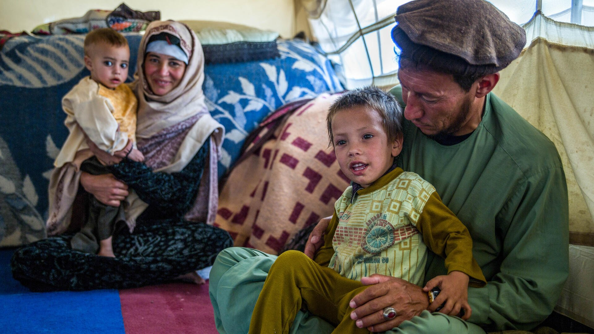 A mother and father in Afghanistan sit on the ground among blankets and pillows, each with a child on their lap. The boy in the front is smiling and his father is looking at him.