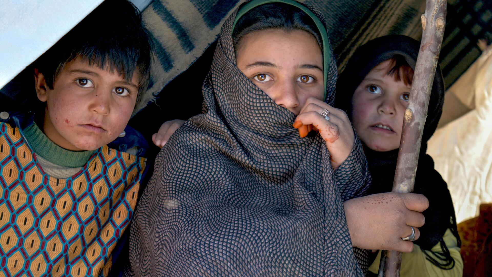 Three Afghan children sit inside a makeshift tent
