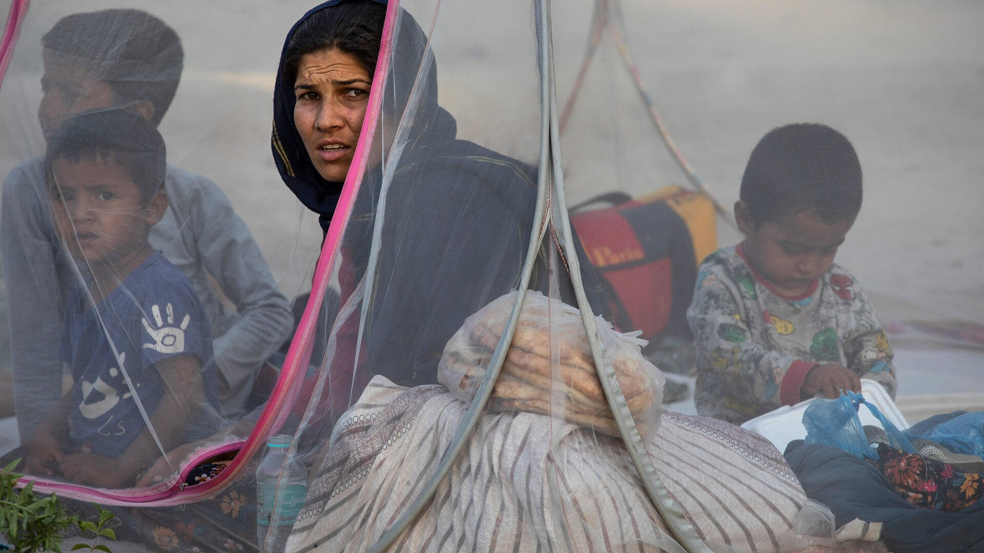 An Afghan mother sits in a tent with her young boys at a makeshift IDP camp.