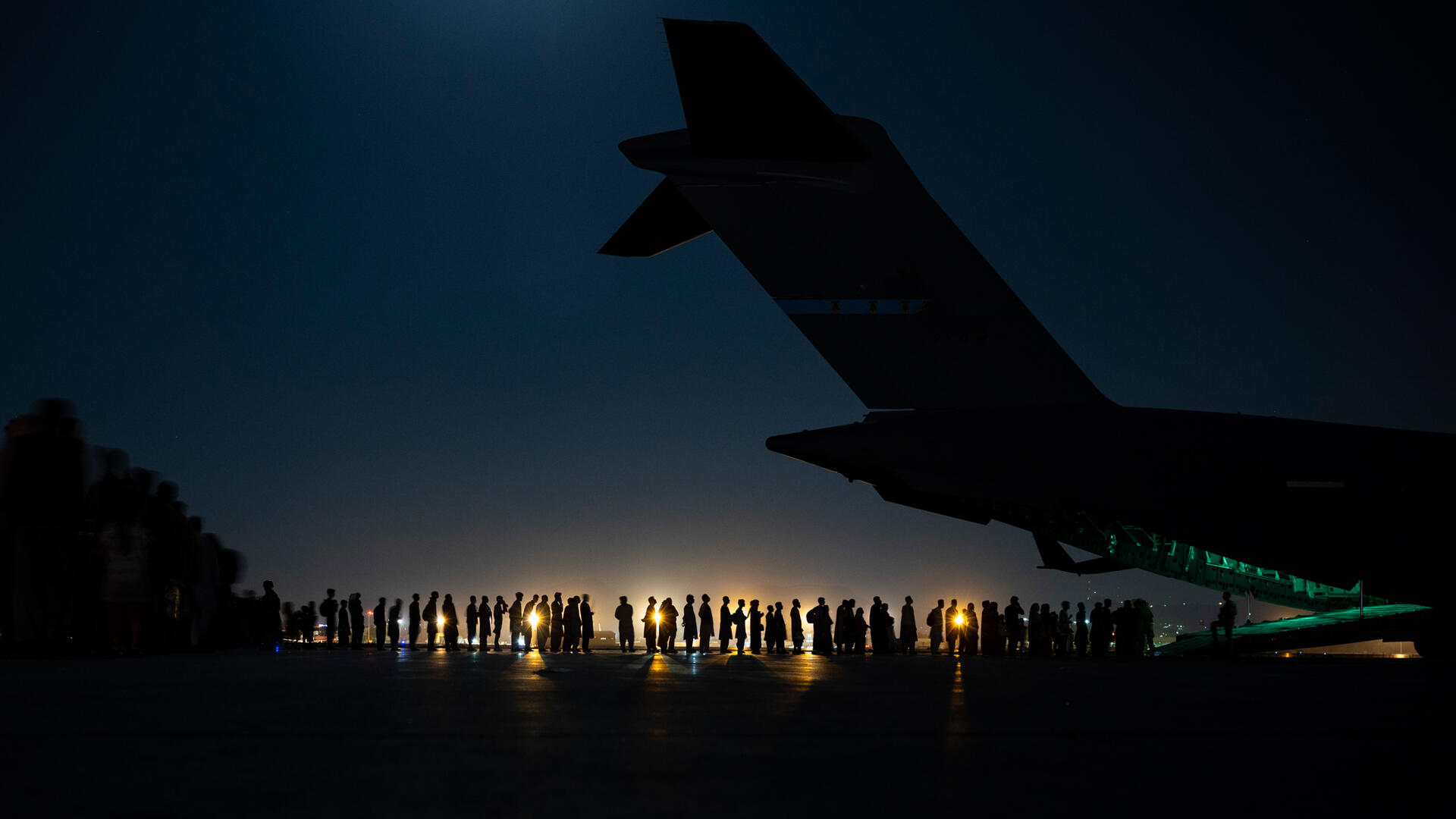 A night shot, with the tail of an airplane in the foreground and a line of people in the background. We can see a light in the distance and just the silhouette of the plane and people.