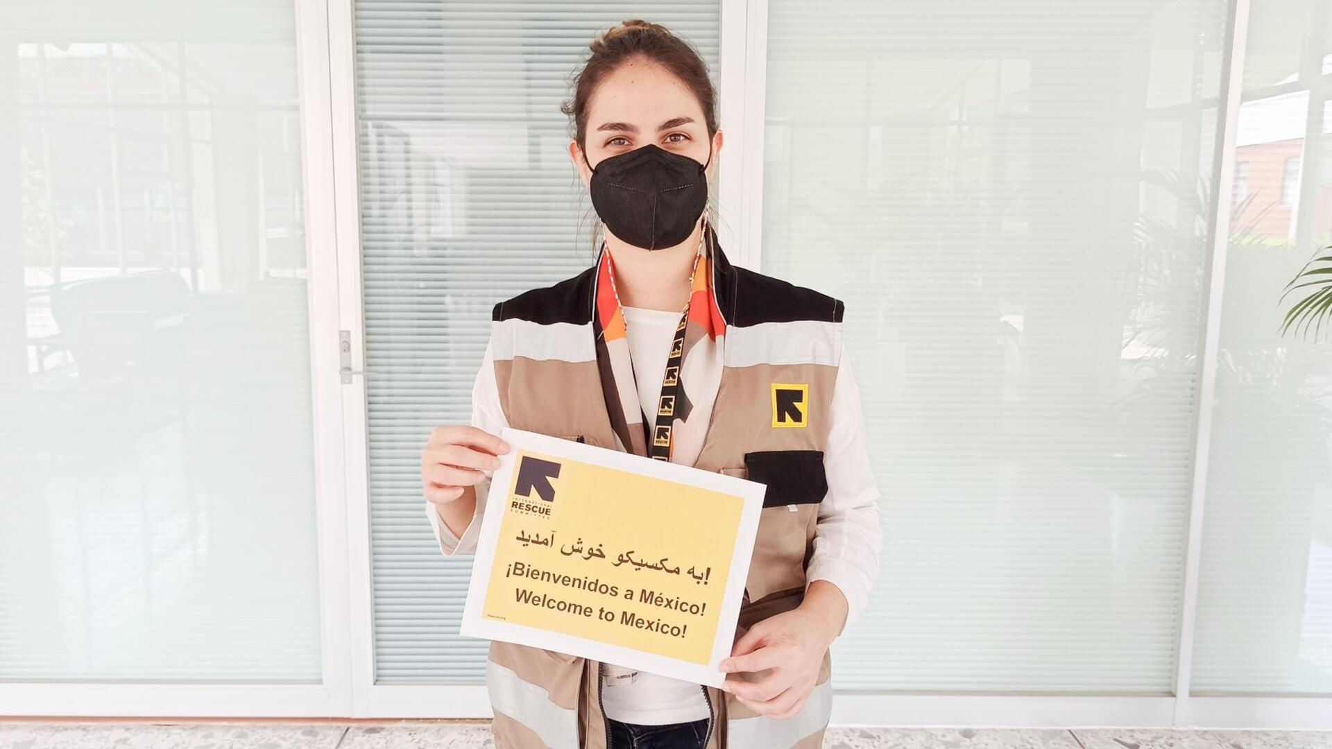 """Fatima, a home visiting officer for the IRC in Mexico, holds a sign that says """"welcome to Mexico"""" in English, Spanish and Dari. She is wearing a mask and an IRC vest."""