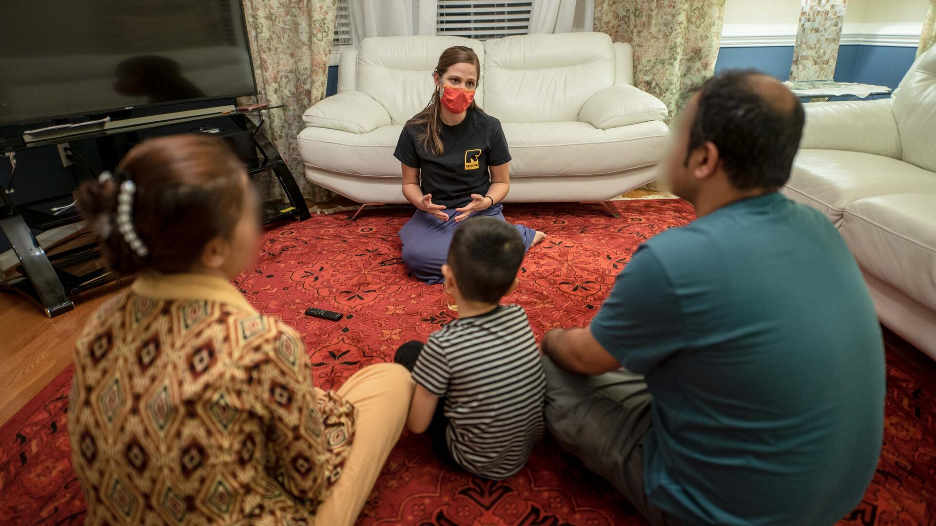 An IRC staff member sits and speaks with an Afghan man, woman, and child.