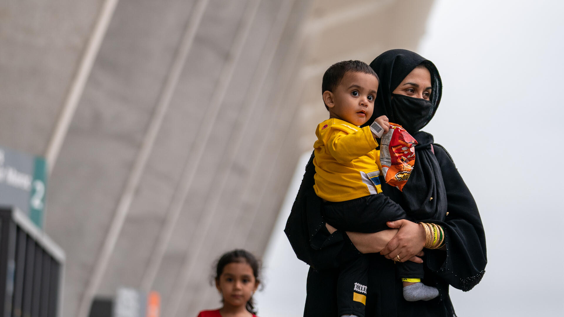 An Afghan woman holds her son as they arrive in the U.S.