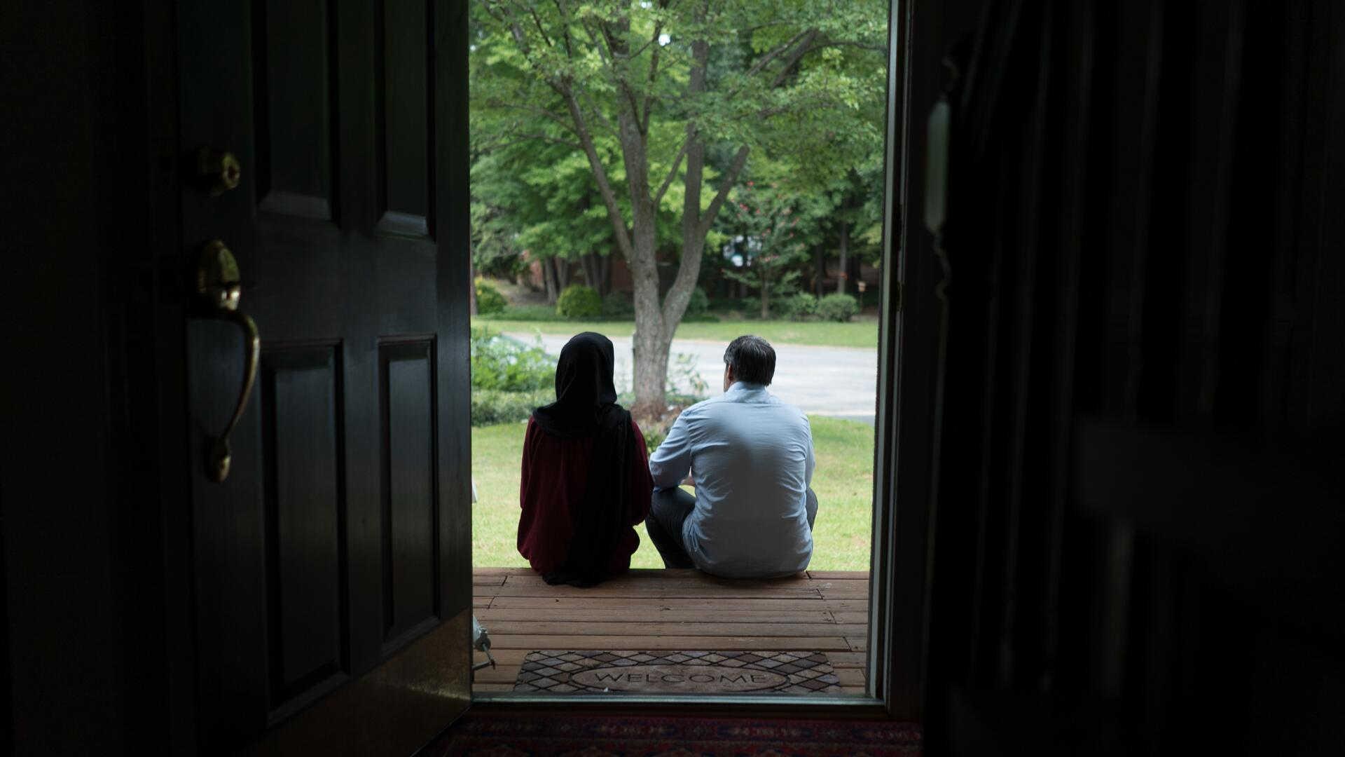 Afghan refugees Fatima, 19, and her father Abdul, 52, sit on the wooden front steps of a Virginia house looking out at the trees in the yard