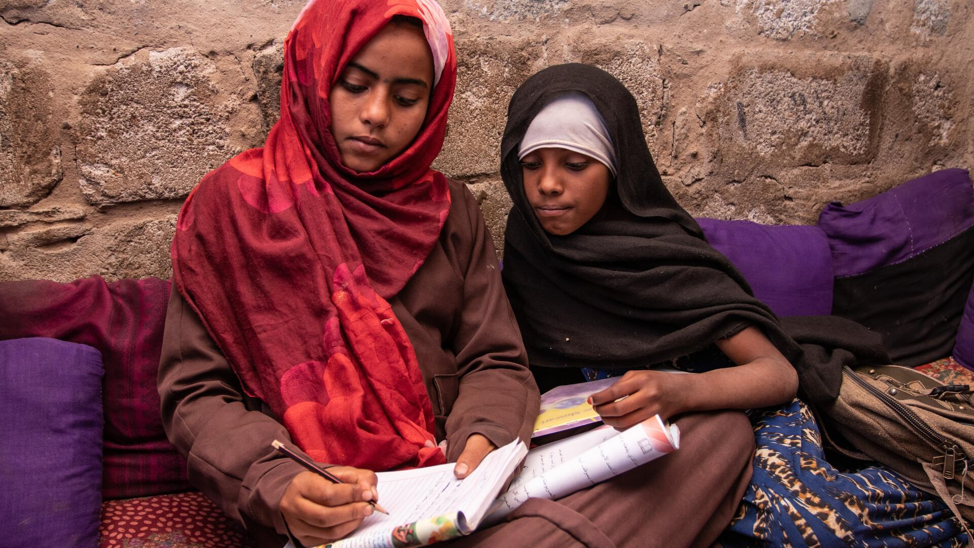 Na'aem, 11, and her best friend Aisha, 10, sit together on the ground studying a school book in a displacement camp in Yemen..