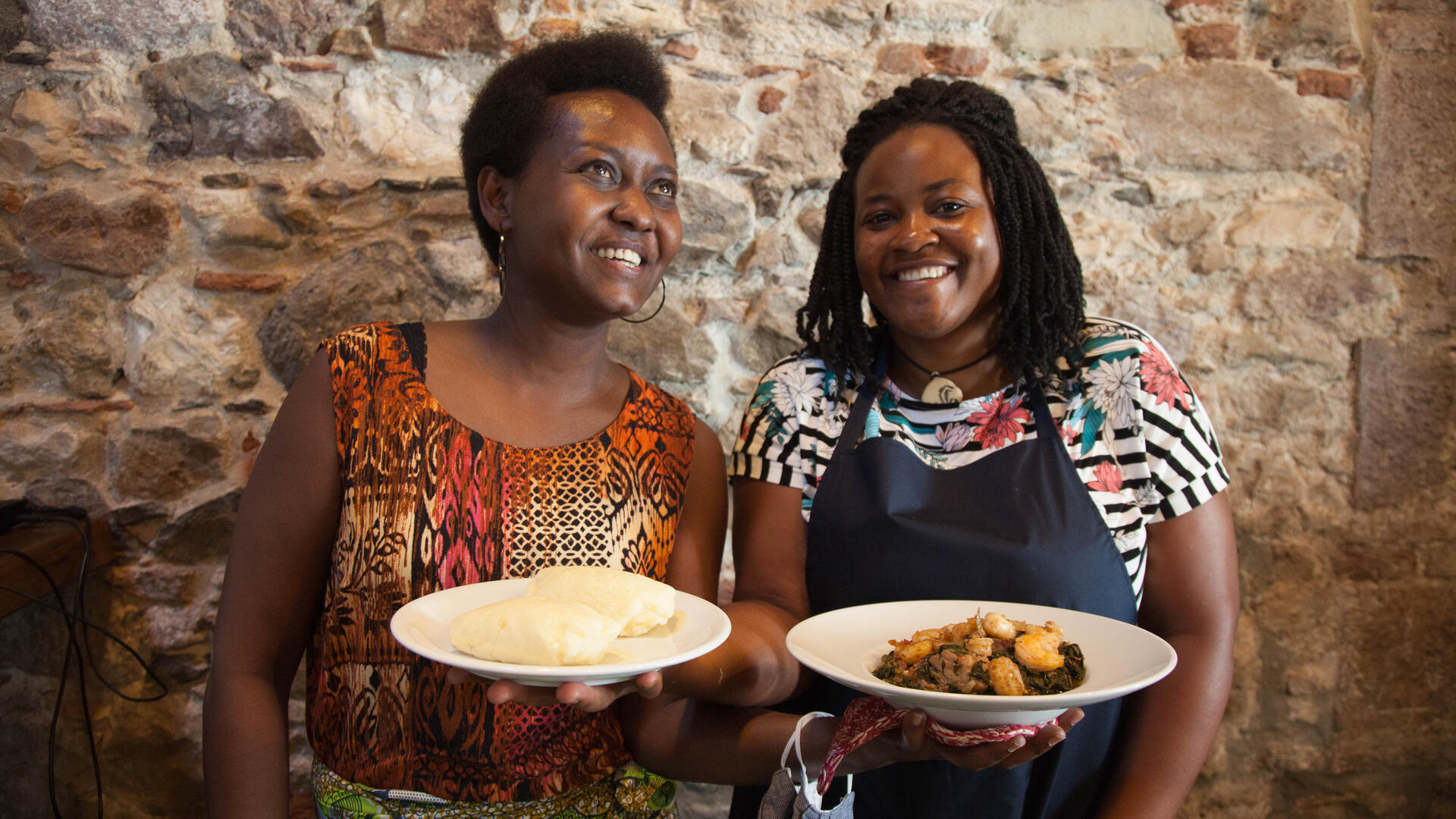 Two women smiling and holding plates of food.