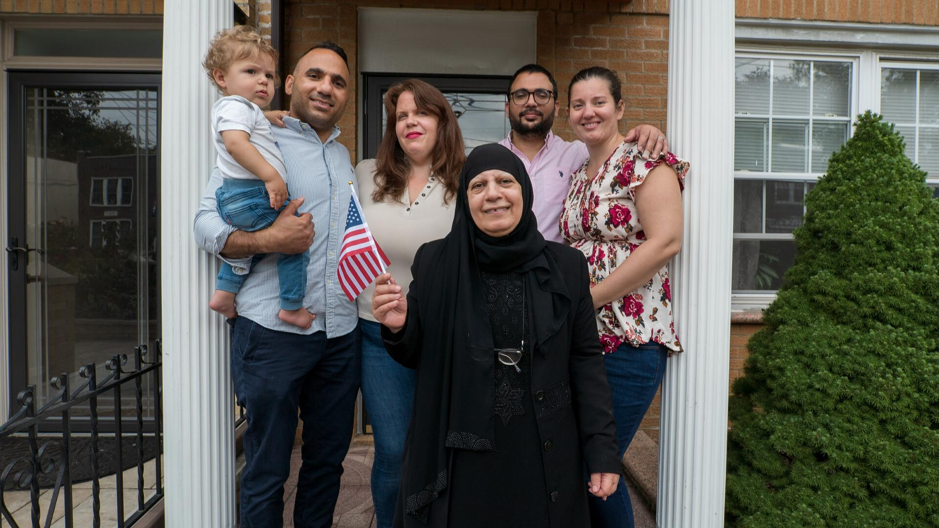 Maha al-Obaidi, a 66-year-old Iraqi woman, stands holding an American flag with her family on the porch of their home in New York City.