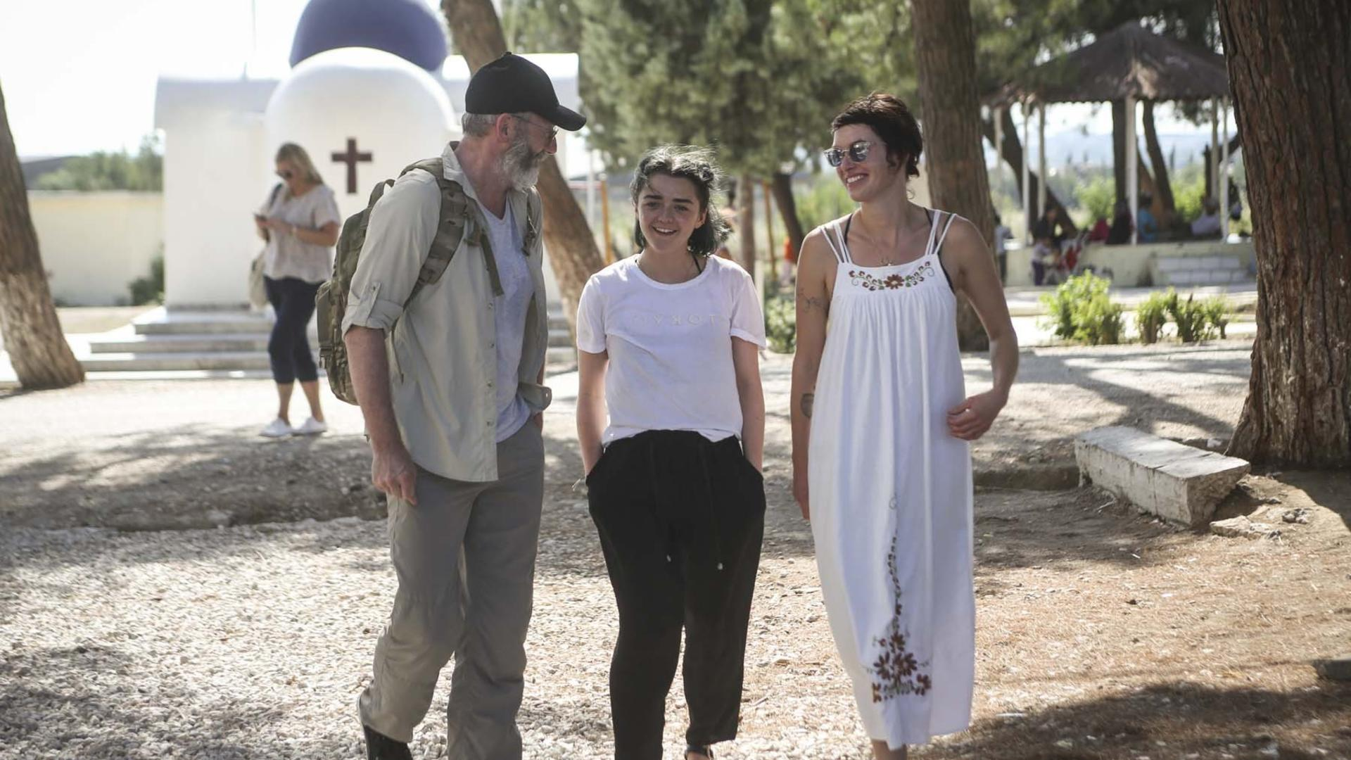 Game of Thrones actors Liam Cunningham, Maisie Williams and Lena Headey walk through a refugee site in northern Greece