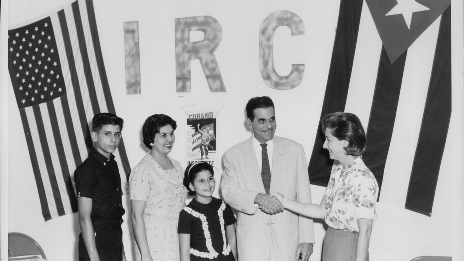A Cuban family of four is greeted by an American IRC worker, standing in front of a wall over which a Cuban flag and a U.S. flag hang side-by-side