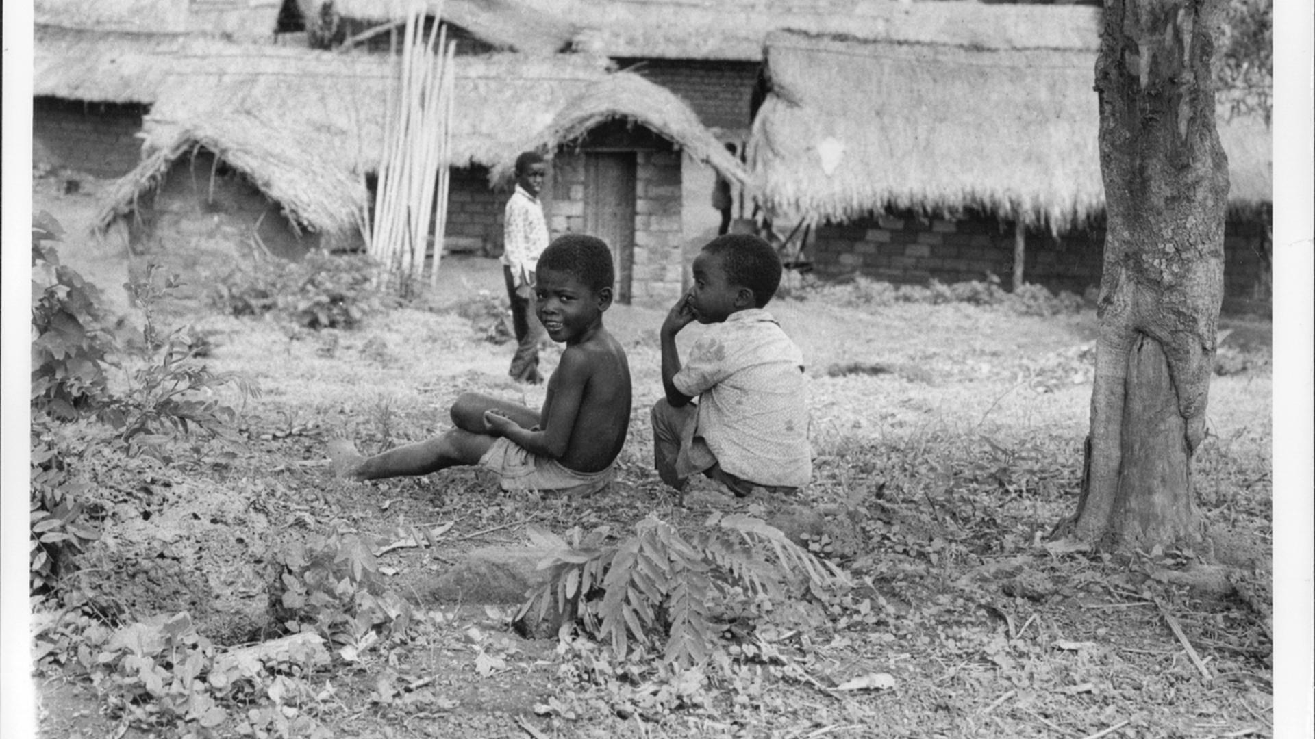 Angolan refugee children sit on the ground outside a row of houses in Zaire.