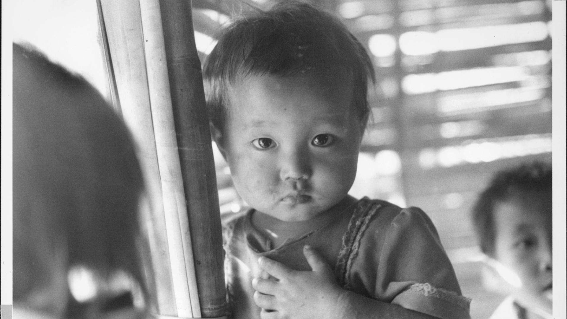 A young girl from Southeast Asia looks at the camera with a serious expression.