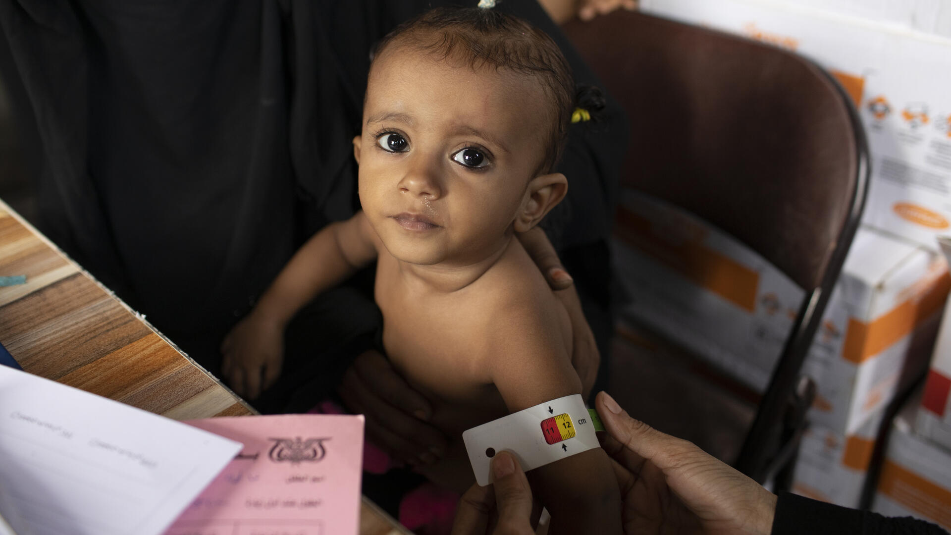 A small child being examined at an IRC clinic in Yemen has her upper arm measured with a MUAC tape, which shows she may be acutely malnourished.