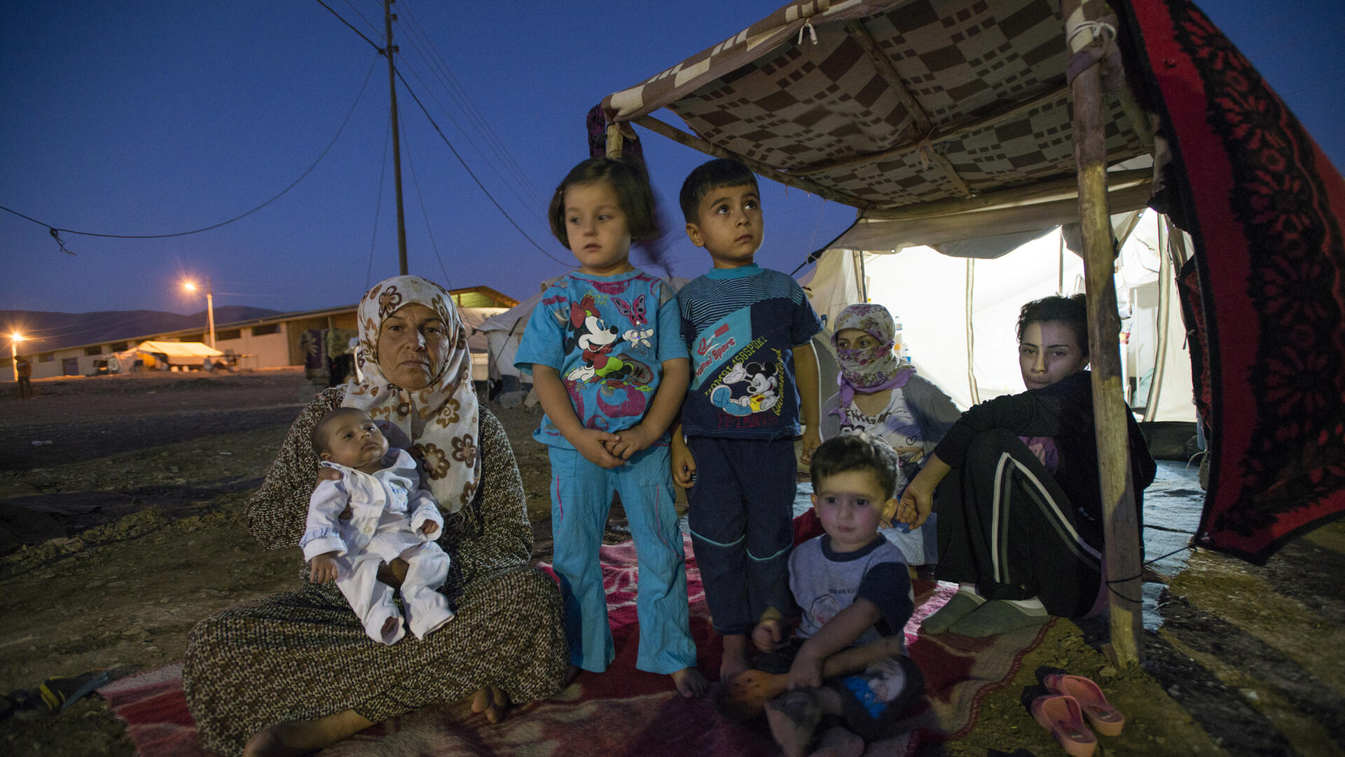 A family made homeless by violence sits outside their makeshift shelter in northern Iraq