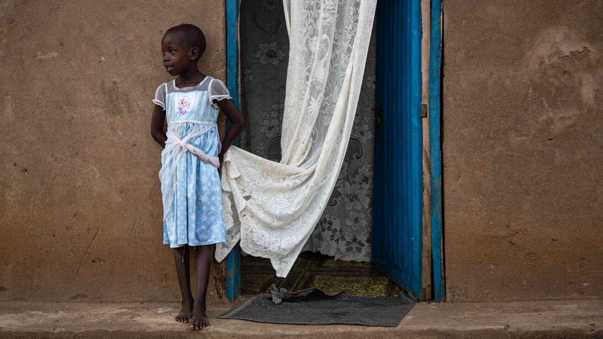 Foni Grace's six-year-old daughter, Nancy, stands outside their home. She is looking to the side and holding the edge of a white curtain.