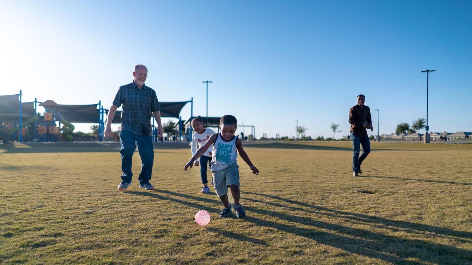 Dave, left, plays with Robert's children, Sandra and Agape who call him Grandpa Dave. They are in a field and the children are kicking a ball.