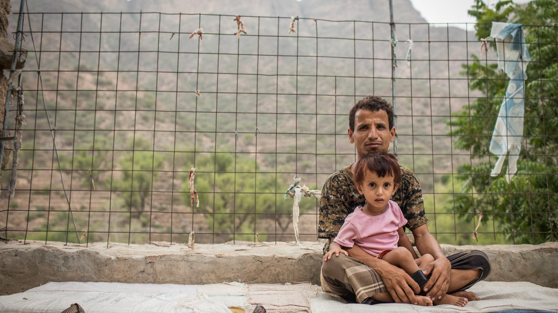 A man sits outside holding his child in his lap in a mountain village in Yemen where an IRC mobile health team provides care to families affected by conflict.