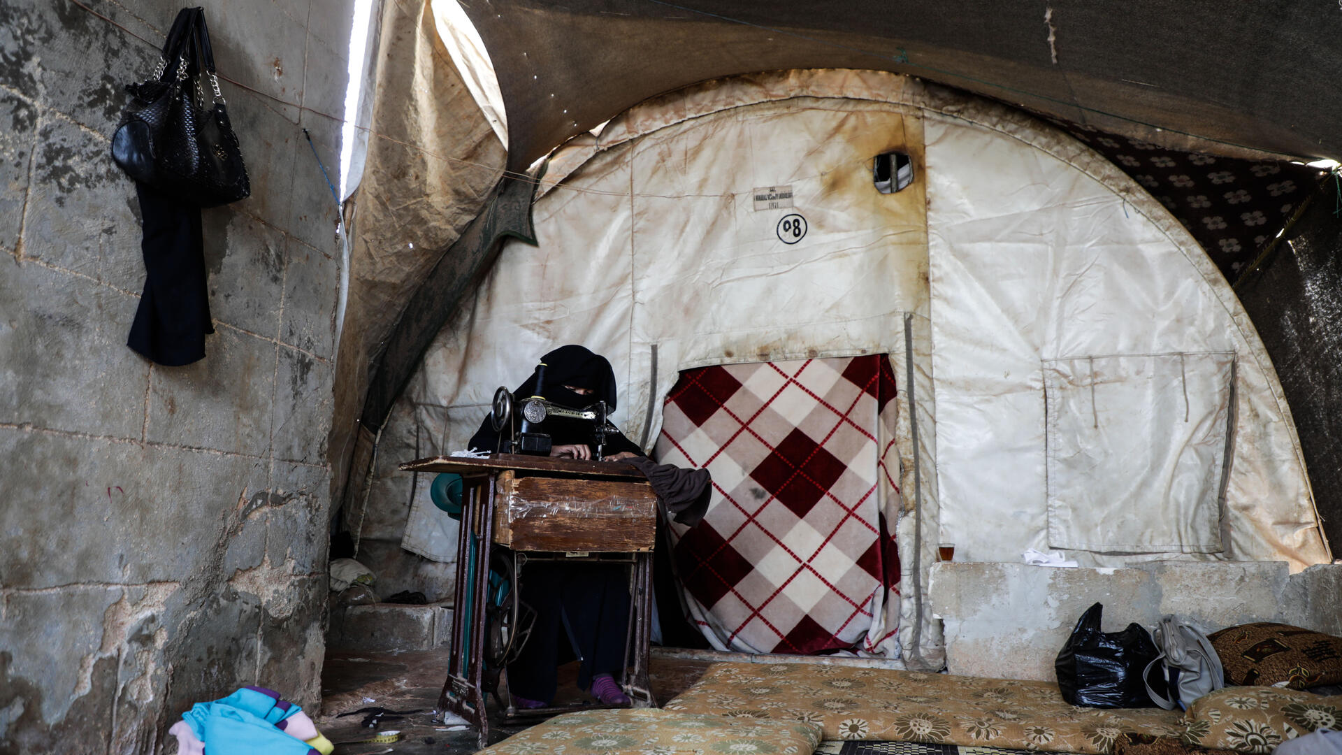 Wa'ad sews face masks at her sewing machine in her makeshift shelter in northwestern Syria.