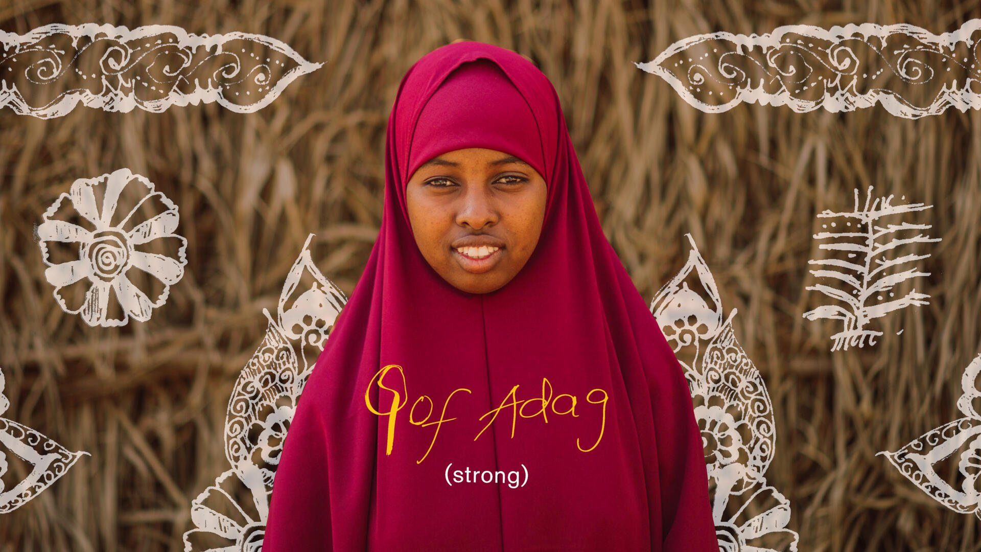 "Suleykha Isaac Mohammed, wearing maroon, smiles for the camera. There is text on the photo that reads ""strong"" in English and Somali."