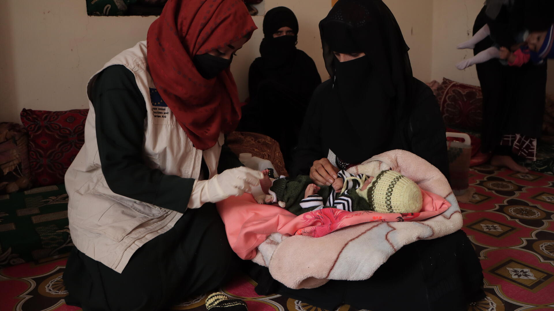 Dr. Bushra sits on a mat alongside her patient, whose newborn baby she is examining.