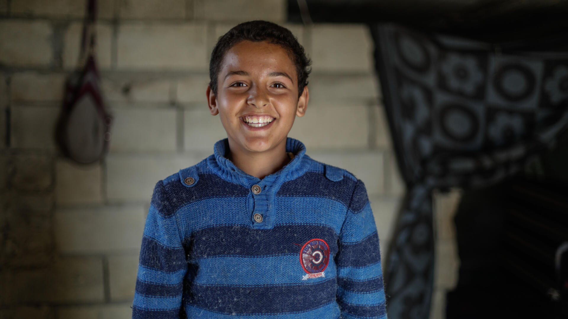 Tareq, wearing a blue and white sweater, smiles for the camera in his home.
