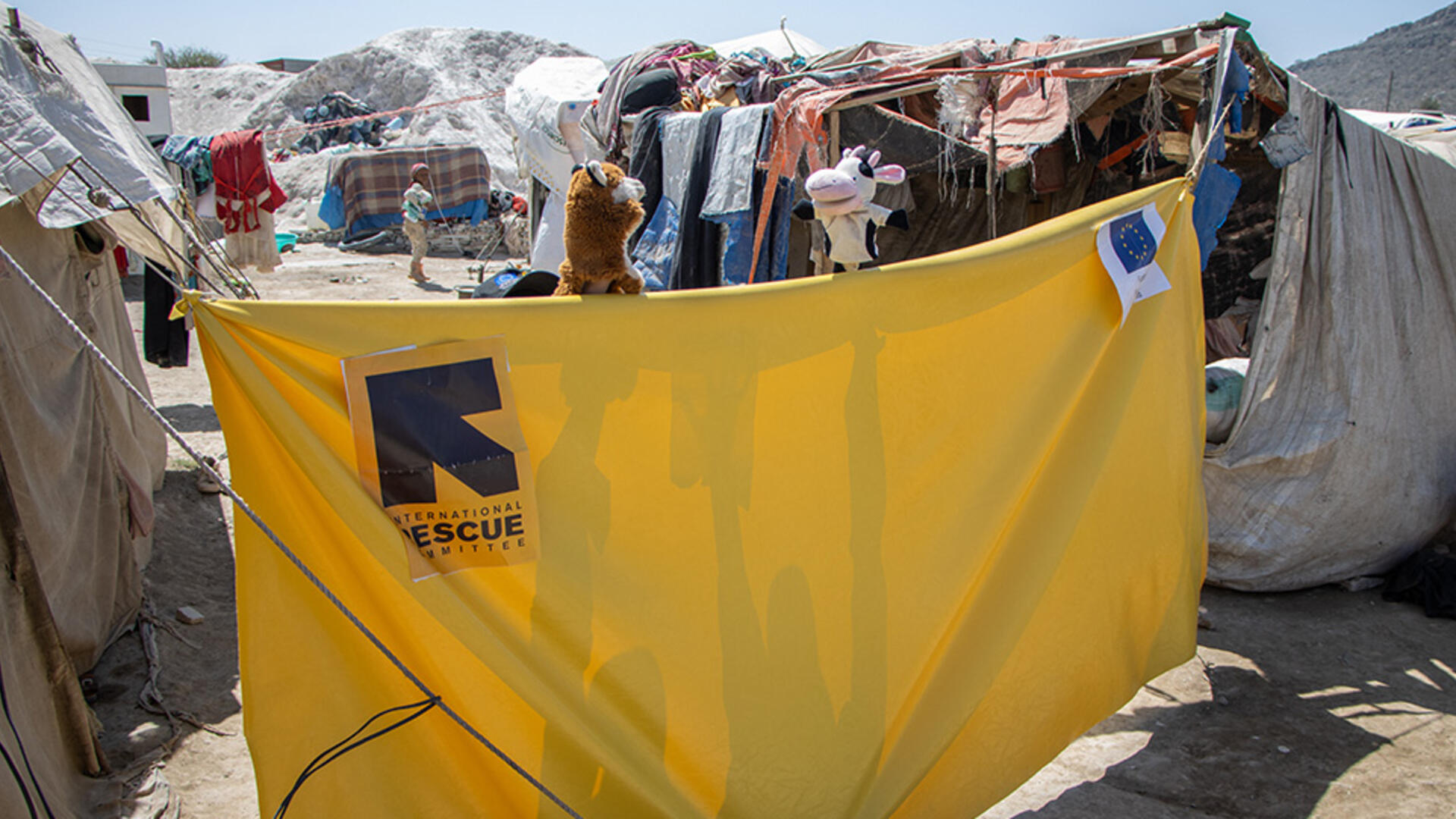 Outside in Al-Manshar camp in Yemen, a yellow tarp is set up between tents. Just above the tarp are a fox and cow puppet, part of the show to teach children about COVID-19.