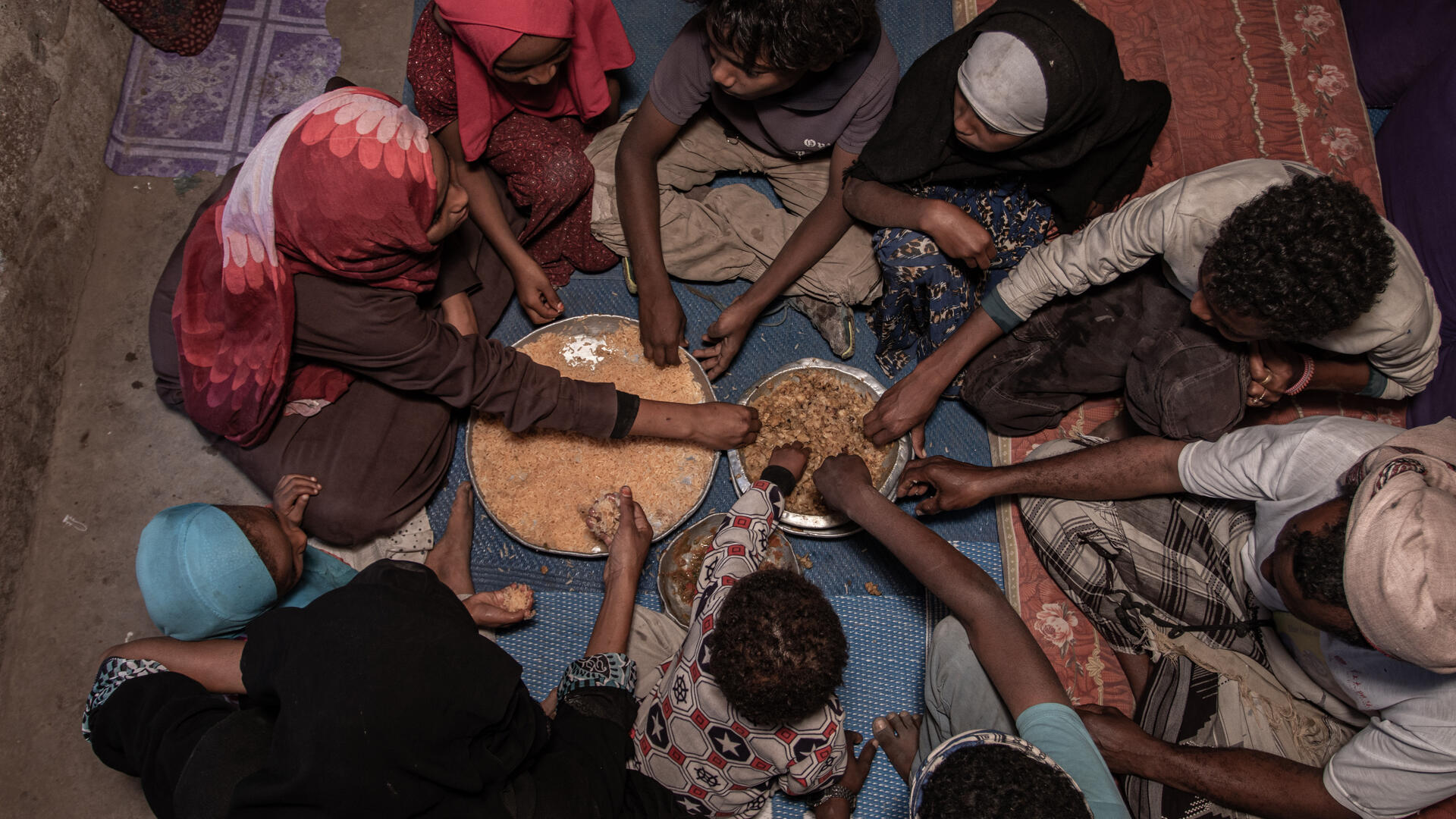A family in Yemen is seated on the floor around plates of food for a meal.