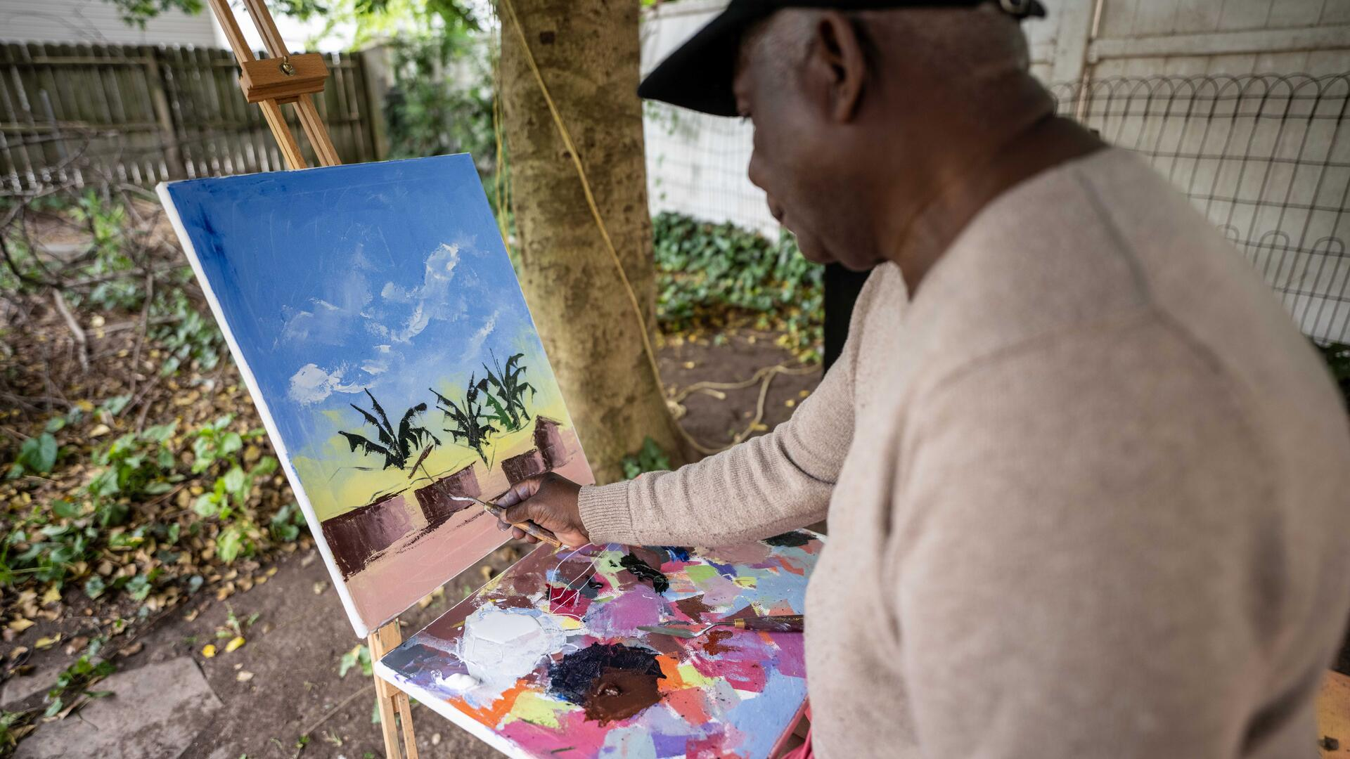 Muyambo Marcel Chishimba, an artist from Democratic Republic of Congo, paints a landscape with oil paints at an easel in his backyard in New Jersey