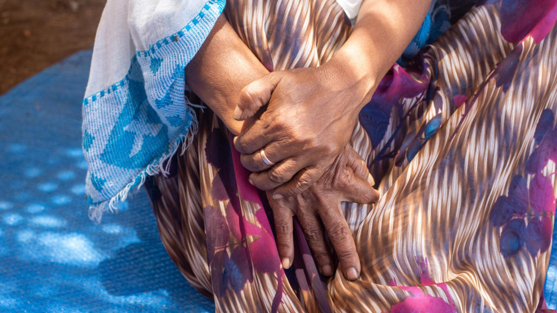 A closeup of 60-year-old Tigrayan refugee Berhan's hands, clasped on her lap.