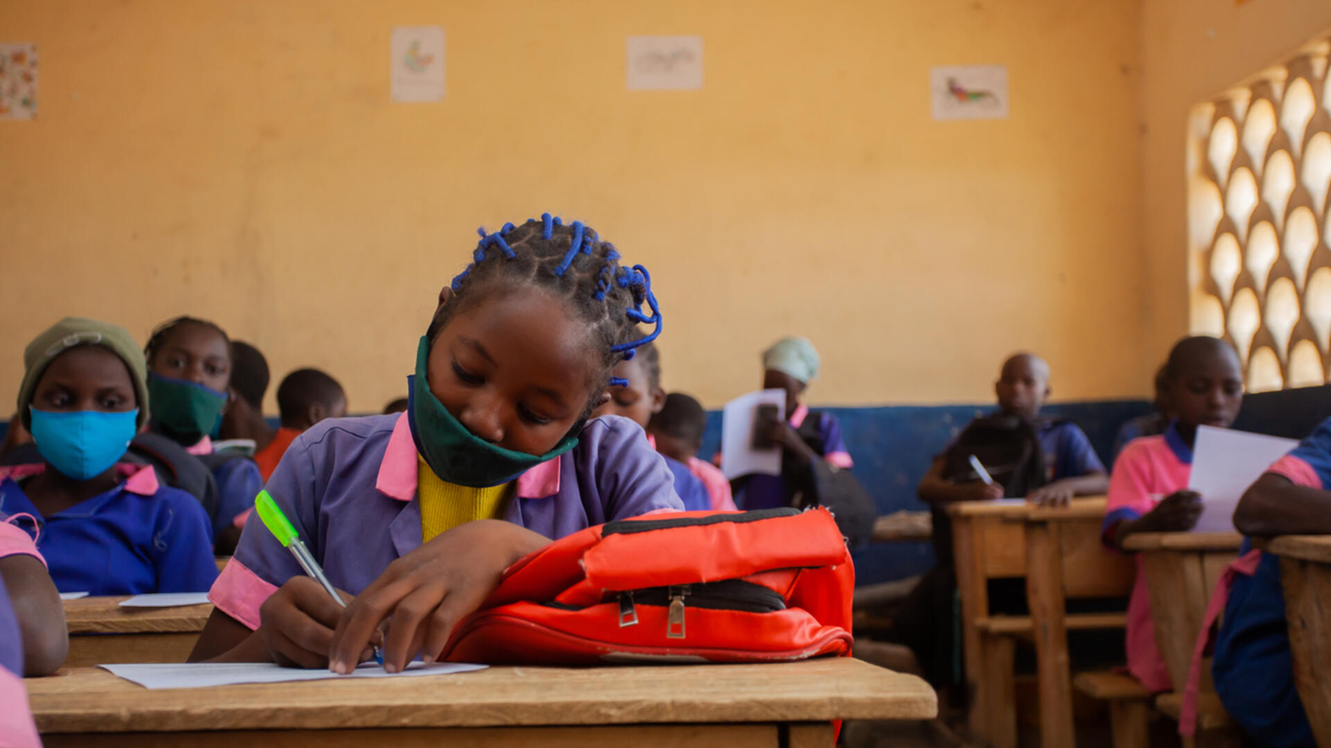 Eleven-year-old Kauvaumah, wearing her school uniform, writes at a wooden desk in her classroom in Cameroon.