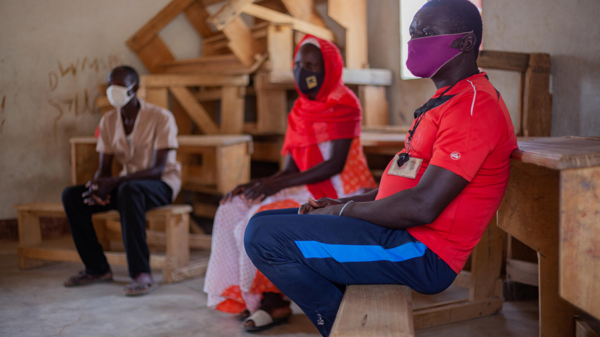 Komonda, 41, seated on a wooden bench, wearing a COVID-19 face mask, at an IRC session for parents of students in northern Cameroon.