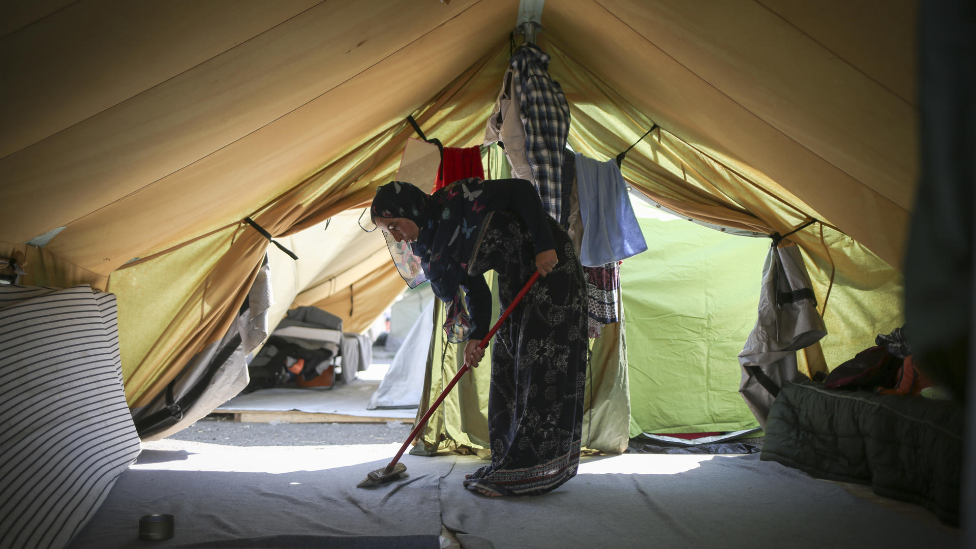 Syrian woman sweeps the floor of her tent in the Alexandria refugee camp