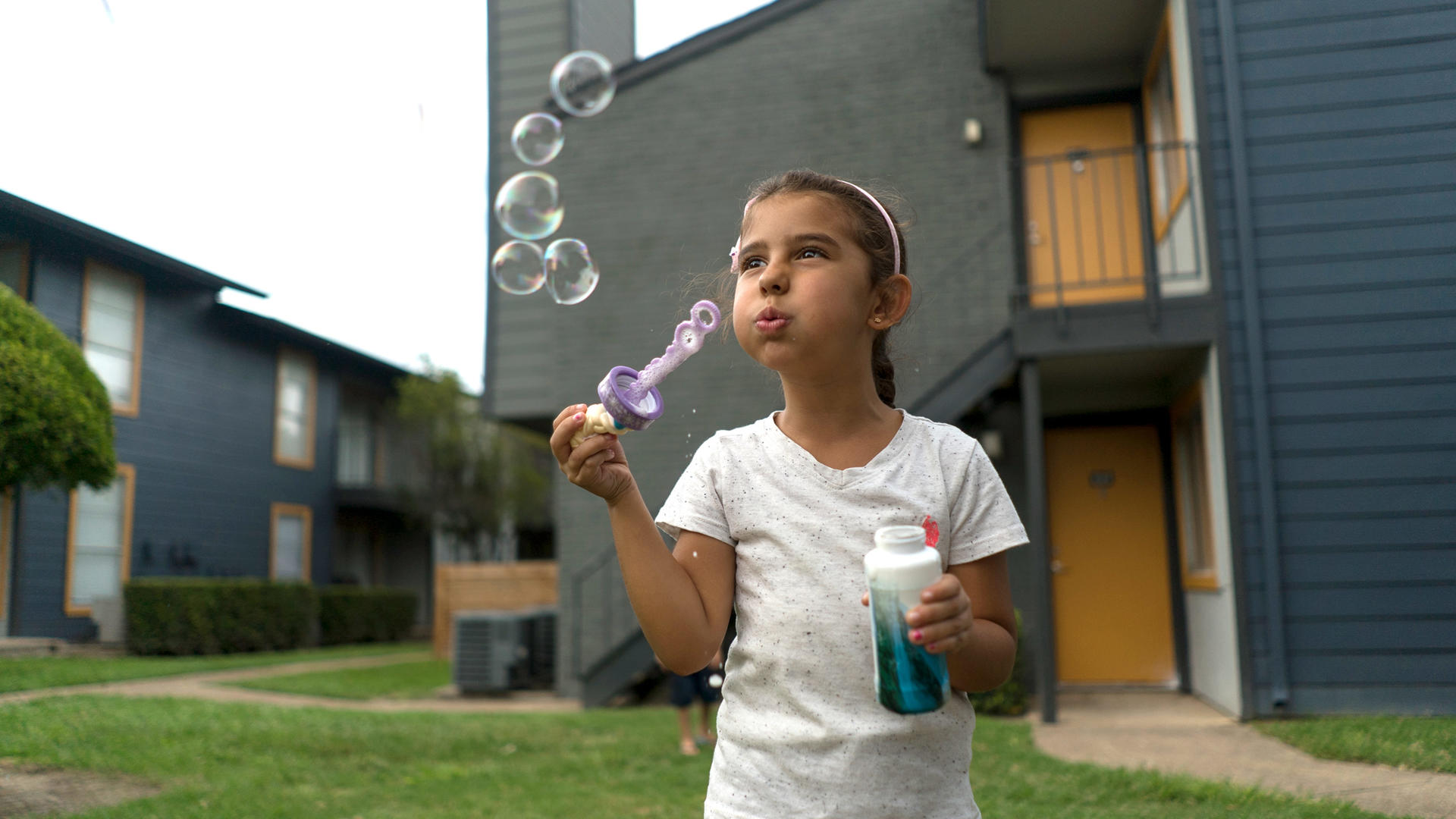 Jori blows bubbles outside her family's apartment