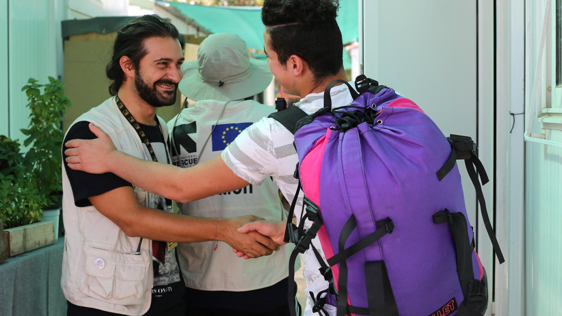 A teenage refugee boy and an IRC aid worker shake hands as the boy leaves a refugee camp in Greece
