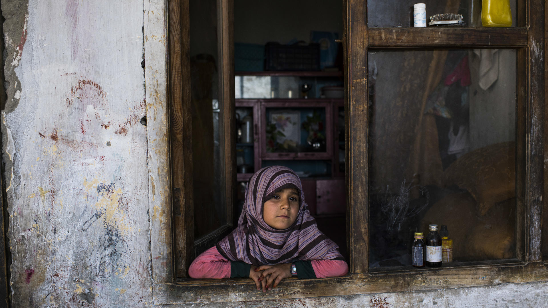 An Afghan girl  looks out the window of her home
