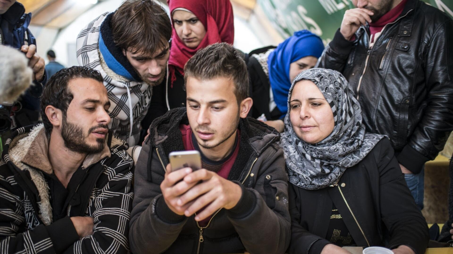 A group of refugees in Sid, Serbia, gather to access Refugee.Info on a mobile phone