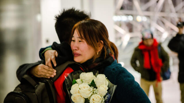 Crying mother hugs son while holding flowers at the airport.