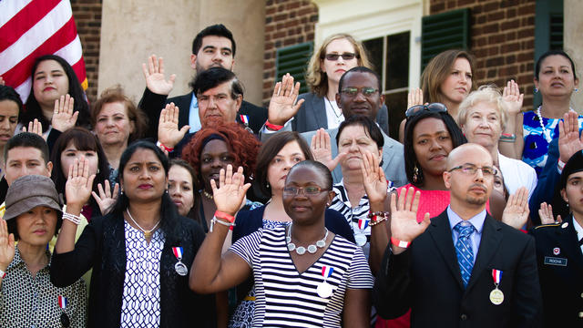Group of people resettled in the U.S. stand together and raise their right hands as they are sworn in as citizens.