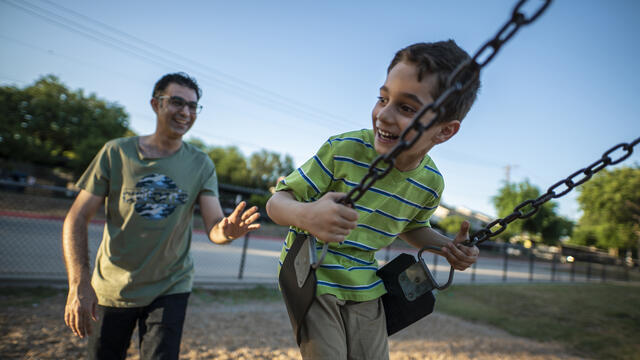 A father, Junaid, pushes his son Ridha on a swing in a playground in Dallas. The family arrived in the U.S. as refugees.