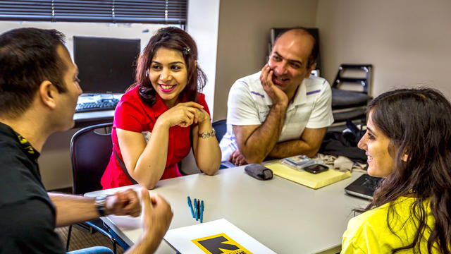 Two men and two women at a resume building workshop sit around a table with papers, pens, and folders, all smiling.