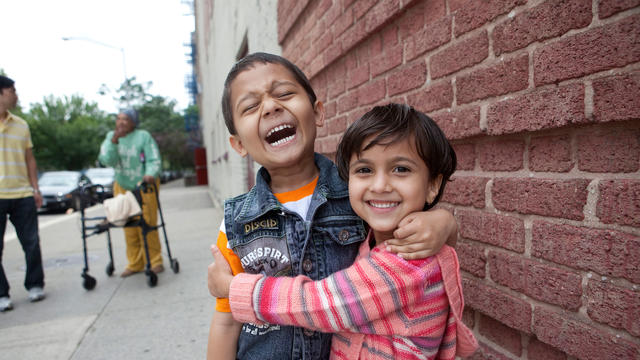 A young boy and girl stand outside in front of a brick wall, laughing and embracing.