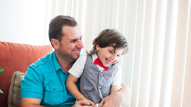 Father sits in chair inside while holding young son on his lap, both happily smiling.