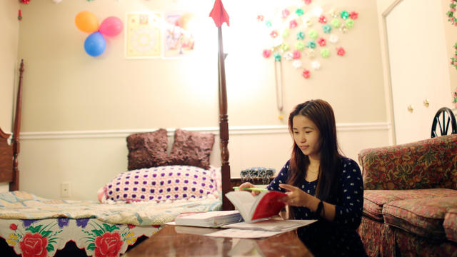Teenage girl sits in her bedroom while doing schoolwork.