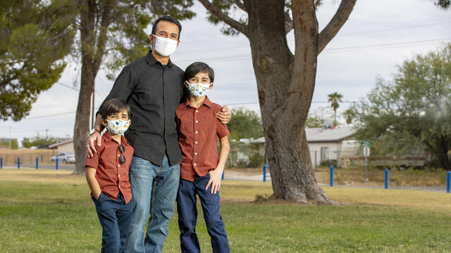 A man stands with his arms around his two young sons in Pima County, Arizona. They are wearing facemasks to protect them from COVID-19.