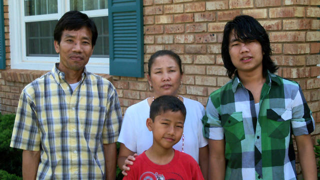Father, mother, and two sons pose for picture in front of their new Abilene home which the IRC helped them move into.